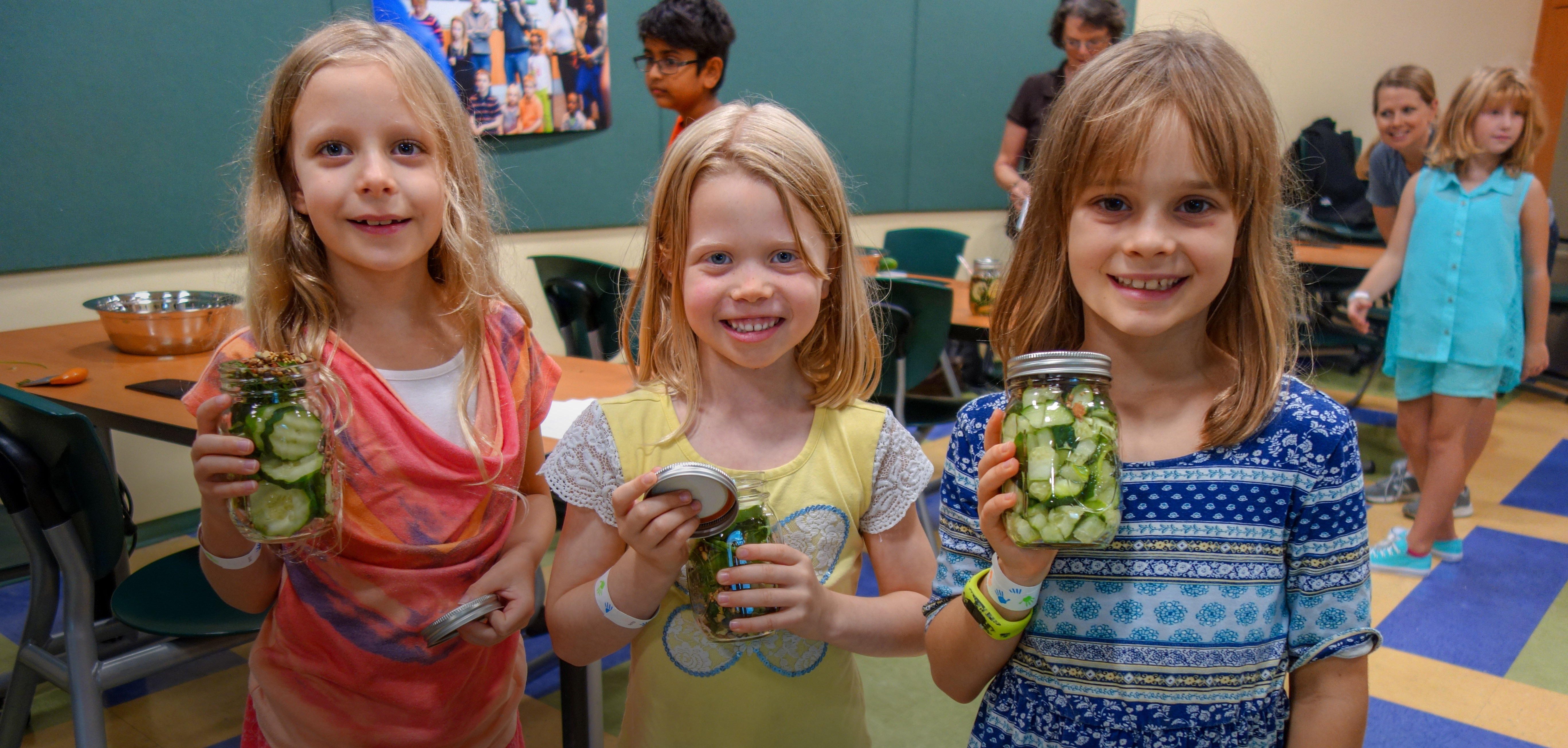 Three girl scouts smiling and holding jars with their science experiment. Programs for Scouts