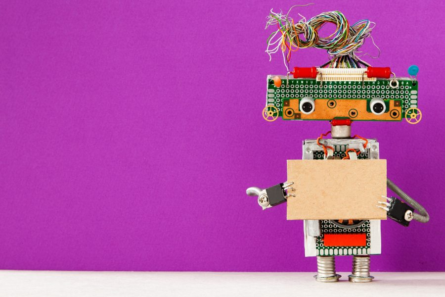 Robot with a cardboard card mockup. Creative design robotic toy holding a blank empty paper poster, purple wall background. Programs for Scouts - Girl Scouts Robotics Workshop