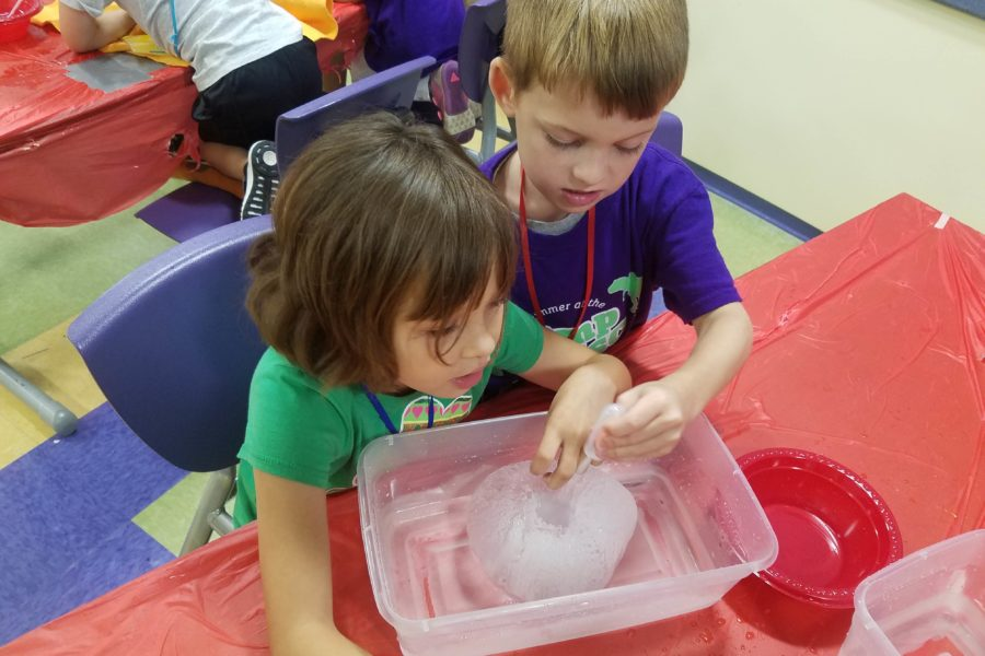 Two campers sitting at a table holding pipettes over a containers filled with water and a big block of ice.