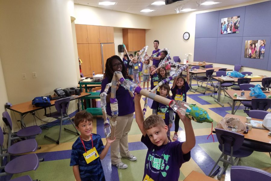 Classroom full of campers and two camp counselors holding up craft of a snake made out of recyclables, like water bottles and paper towel rolls.