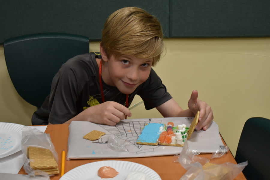 Boy sitting at table smiling with his ginger bread building.
