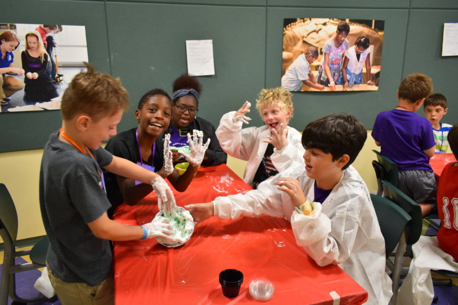 Group of campers around a table. Front left kid and front right kid have their hands in slime in a bowl. Back left and back right campers are leaning over the table and holding up their hands covered in slime. Back center is a camp counselor smiling.