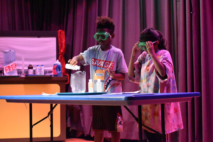 Two campers with colorful labcoats and protective goggle on behind a table and in front of curtains. Camper on the left is pouring a liquid into a larger container. Camper on the right is adjusting her goggles.