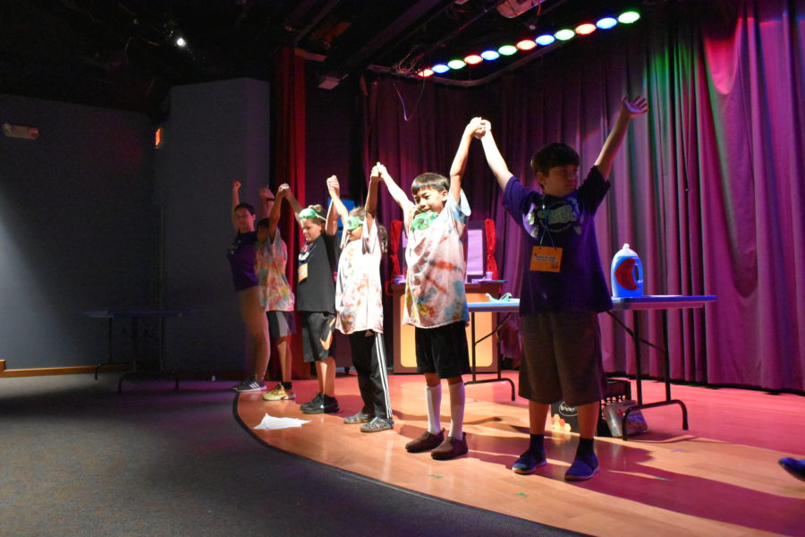Campers standing in front of table on MSC Theater stage. The spot light is shining on them and campers are holding hands with their hands up.