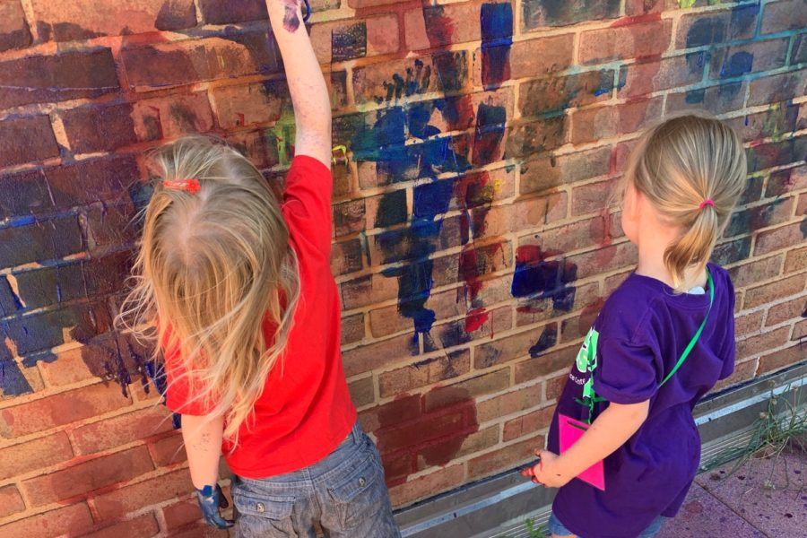 Two little girl campers painting on on a brick wall that already has a bunch of paint on it
