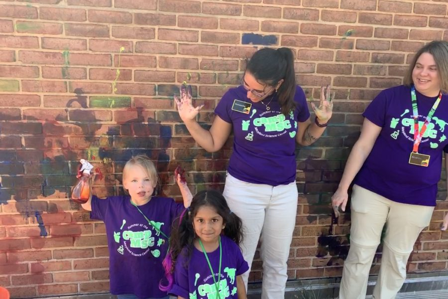 Two young campers and two camp counselors standing in front of brick wall with paint on it. Camper on the left and counselor second to the right are holding up their hands with paint on them.